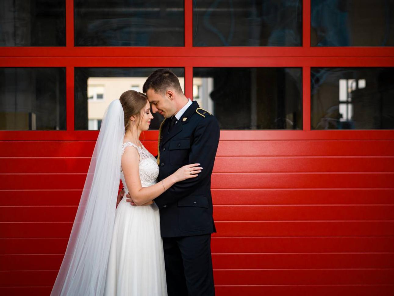 Para Młoda na tle czerwonych drzwi straży pożarnej